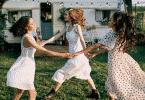 Mulheres sorrindo e dançando em círculo