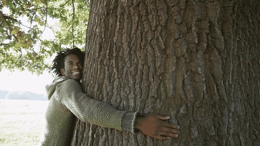 Homem sorrindo e abraçando uma árvore