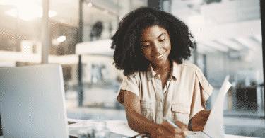 Mulher sorrindo enquanto trabalha