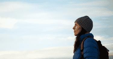 Mulher com roupas de frio e mochila olhando para o horizonte