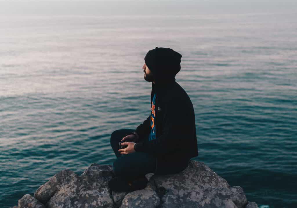 Homem branco sentada numa pedra no mar.