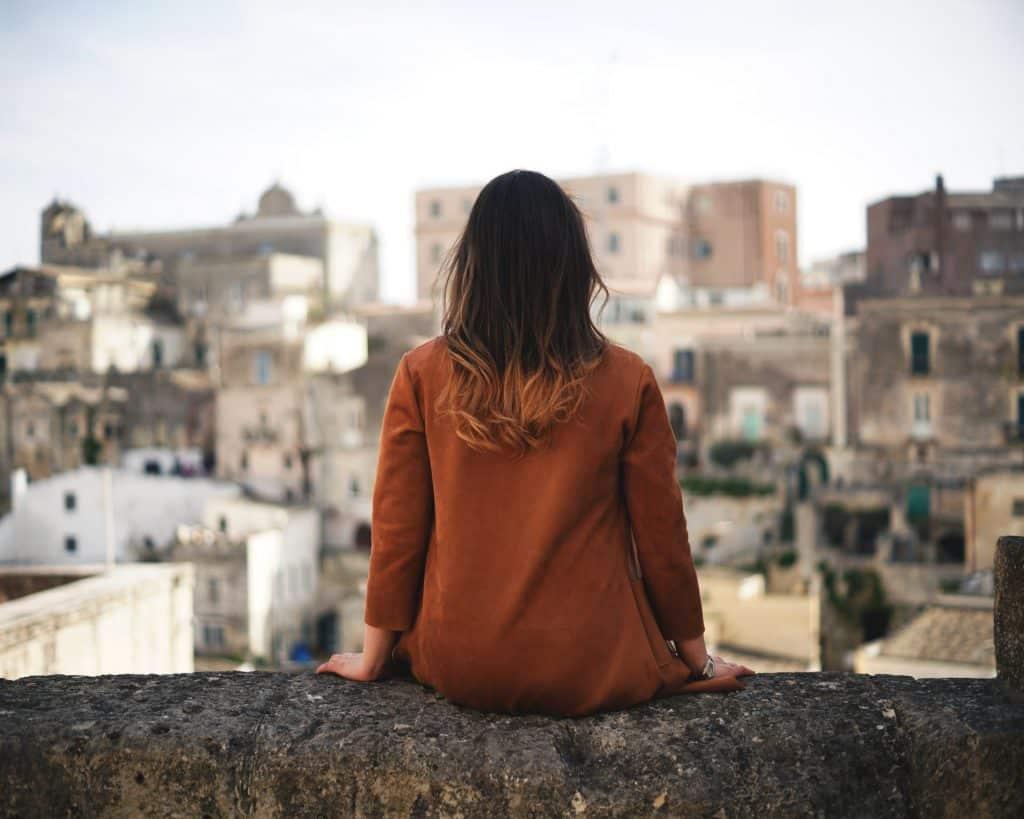 Mulher branca sentada no parapeito de um prédio.