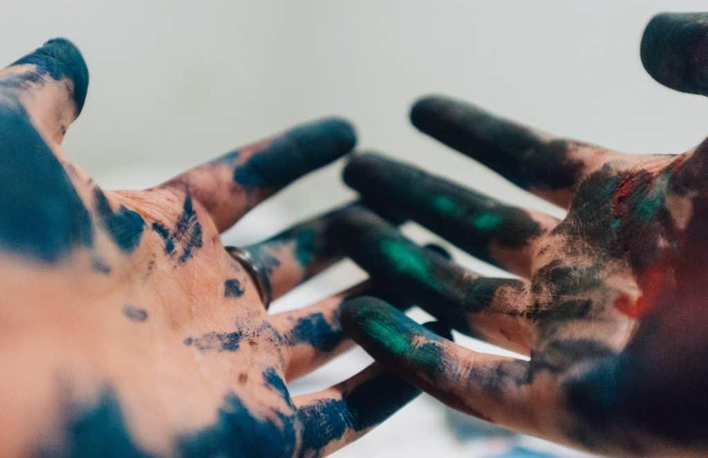 Mãos brancas sujas de tinta.