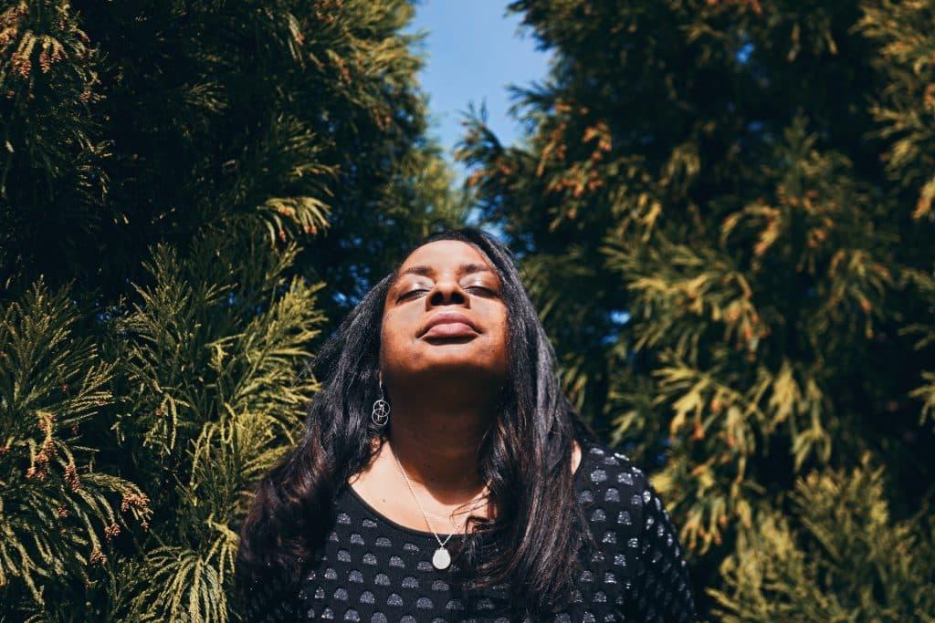 Mulher negra de olhos fechados e plantas atrás.