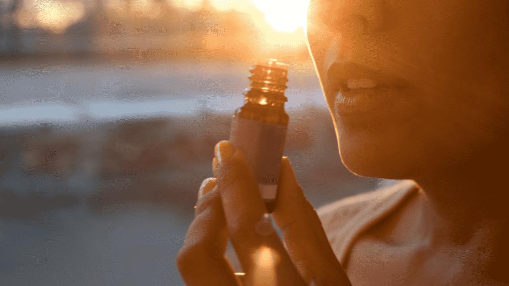 Mulher cheirando um óleo essencial.