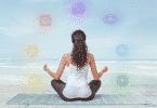 Mulher meditando. Ao seu redor há os símbolos dos sete chakras.