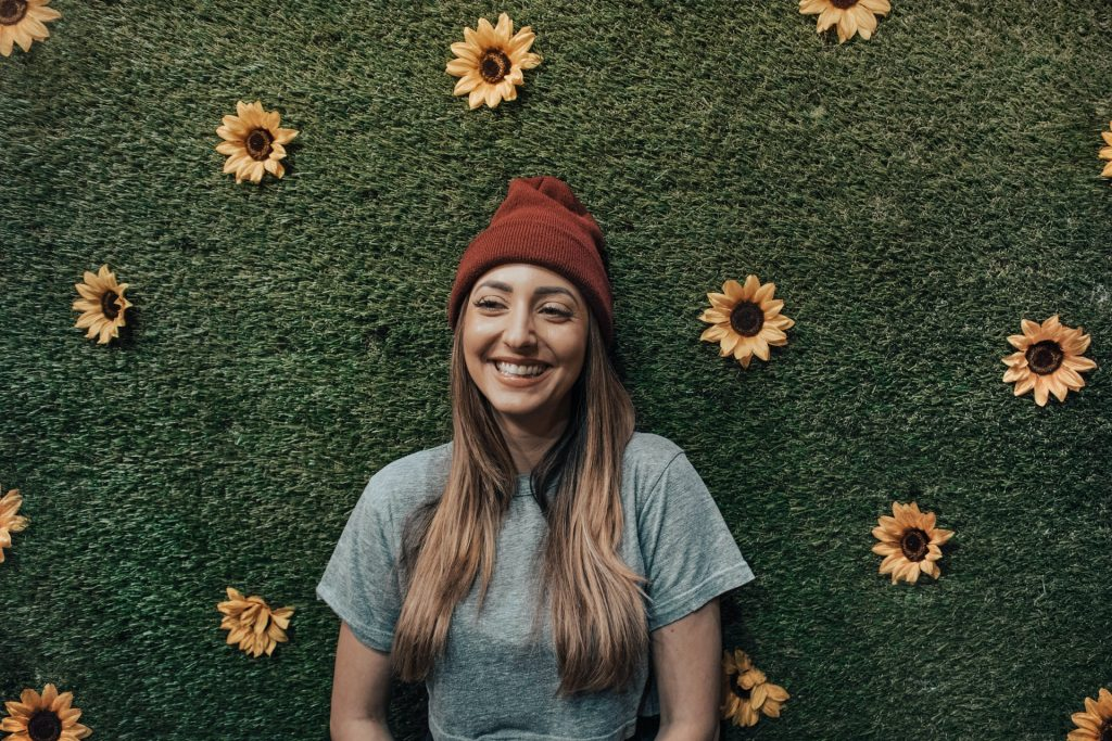 Mulher branca sorrindo numa parede de girassóis.