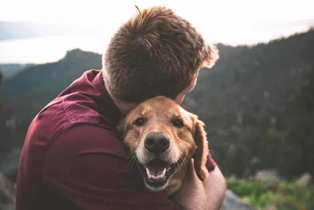 Homem branco abraçando cachorro.