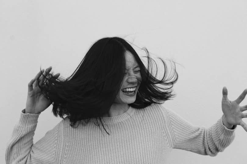 Mulher branca sorrindo balançando a cabeça.