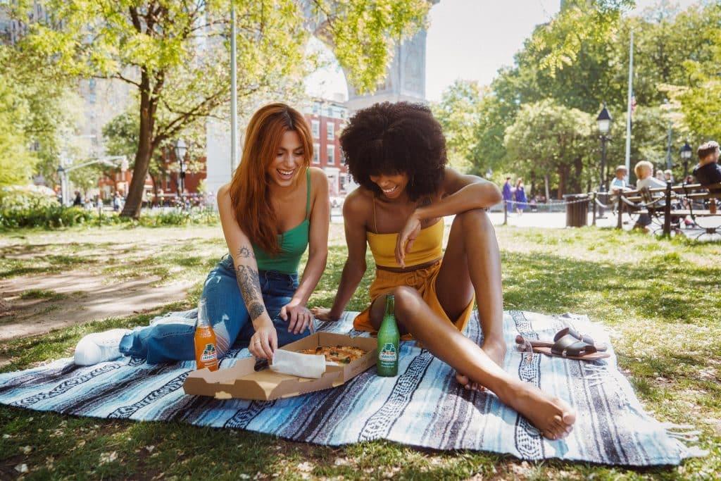 Mulheres branca e negra comendo pizza na grama.