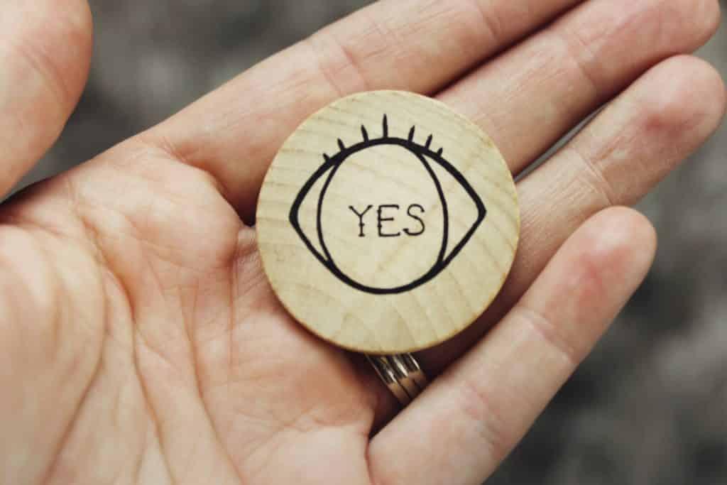 """Pessoa branca segurando círculo de madeira com um olho e a palavra """"yes"""" desenhados."""