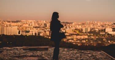 Silhueta de mulher no topo de uma cidade.