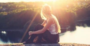 Mulher branca sentada olhando paisagem.