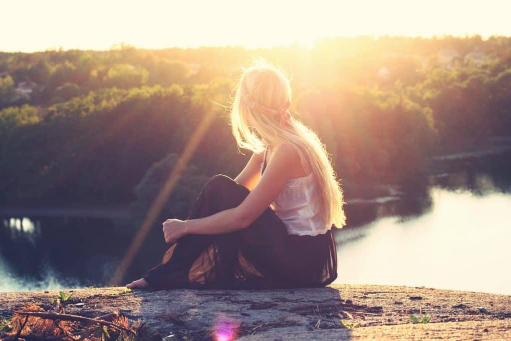 Mulher branca sentada numa pedra olhando o Sol.
