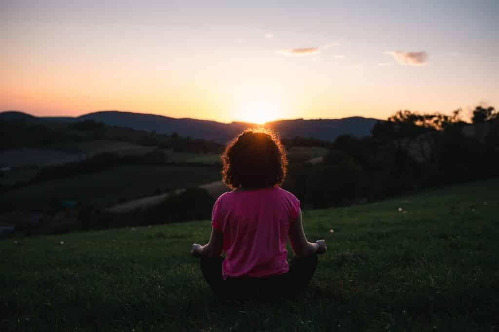 Mulher sentada numa grama meditando.