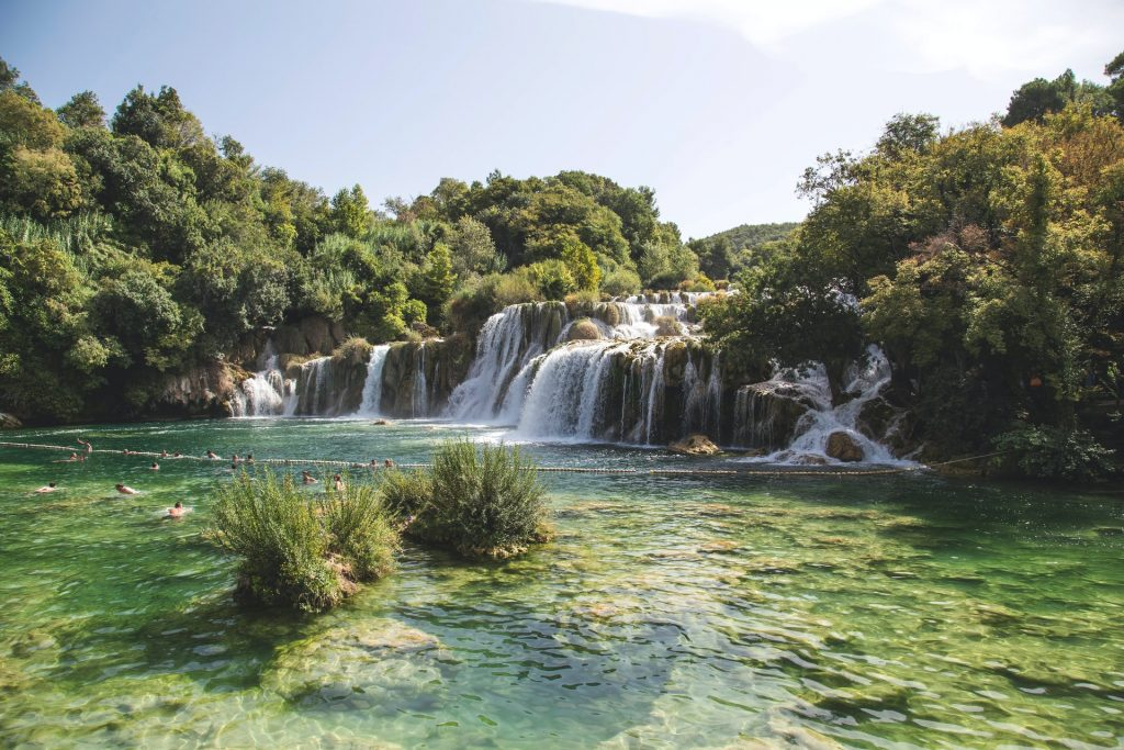 Cachoeira pequena com árvores em volta.