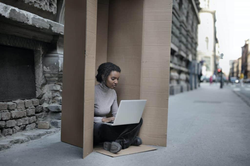 Mulher dentro de uma caixa usando seu laptop