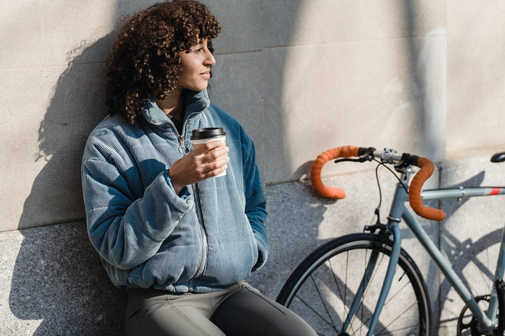 Mulher tomando café e observando a paisagem.
