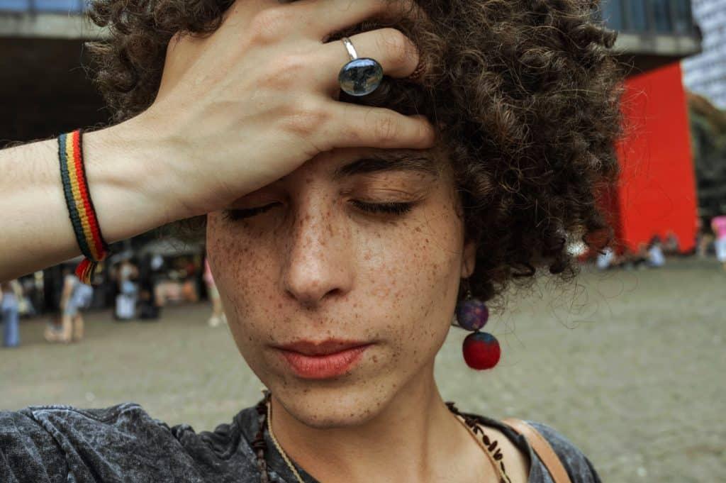 Mulher de olhos fechados com a mão em seu rosto