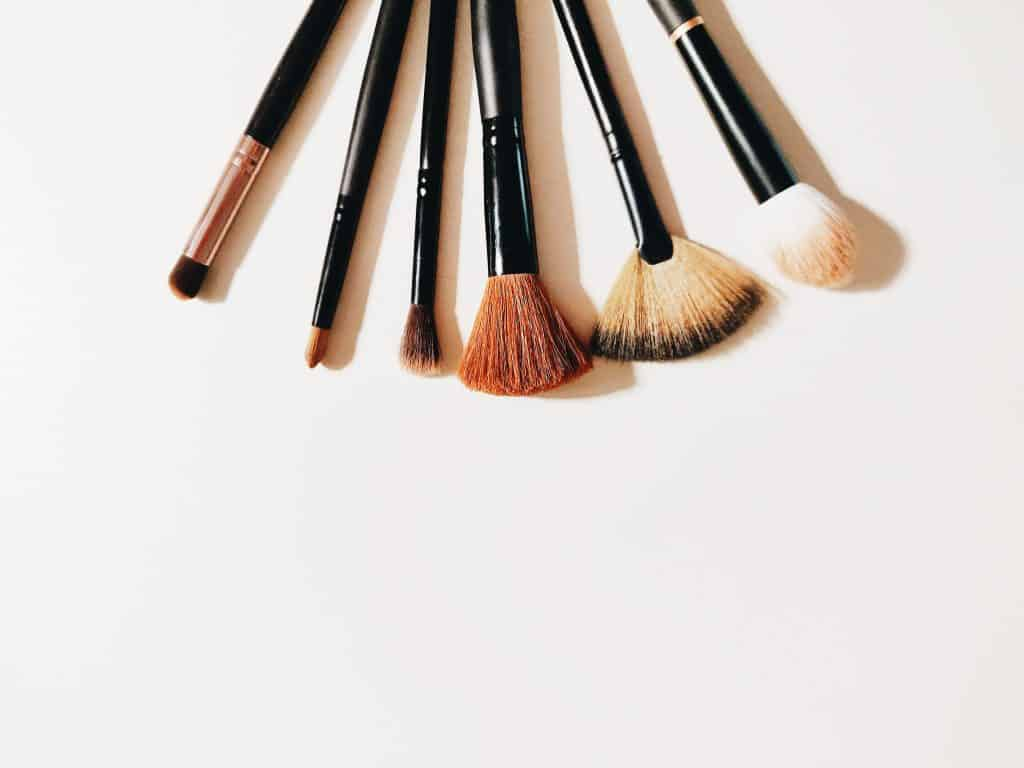 Diferentes pincéis de maquiagem em cima de uma mesa