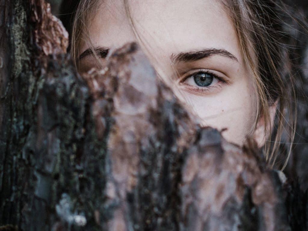 Foco nos olhos de uma mulher que está atrás de um troco de árvore