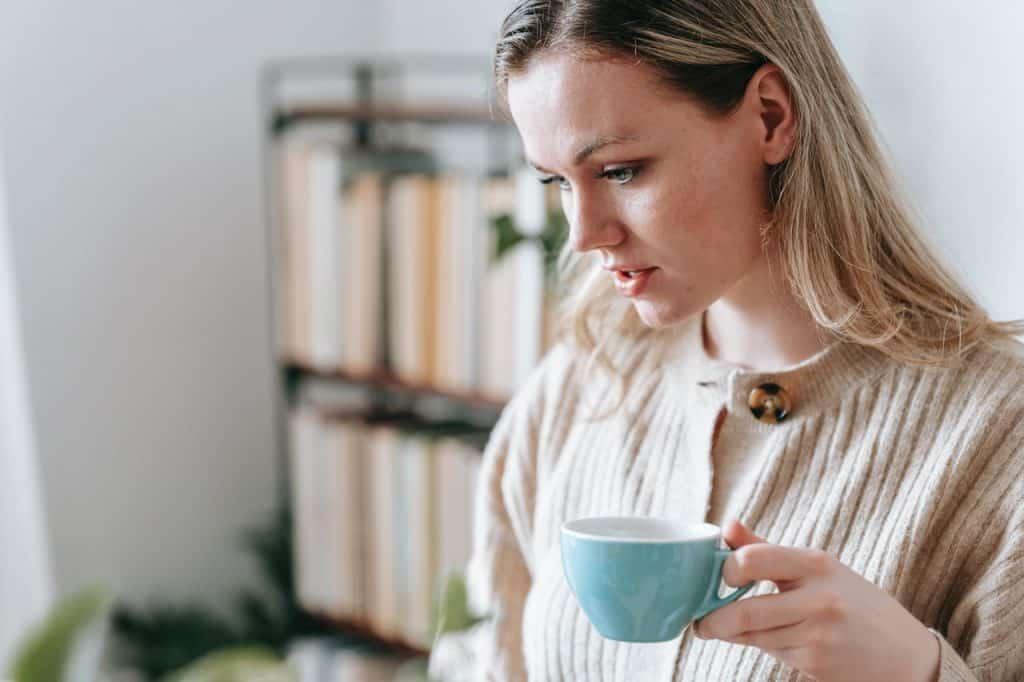 Mulher segurando uma xícara de café com semblante pensativo.