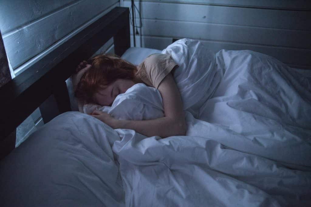 Mulher deitada em uma cama dormindo.