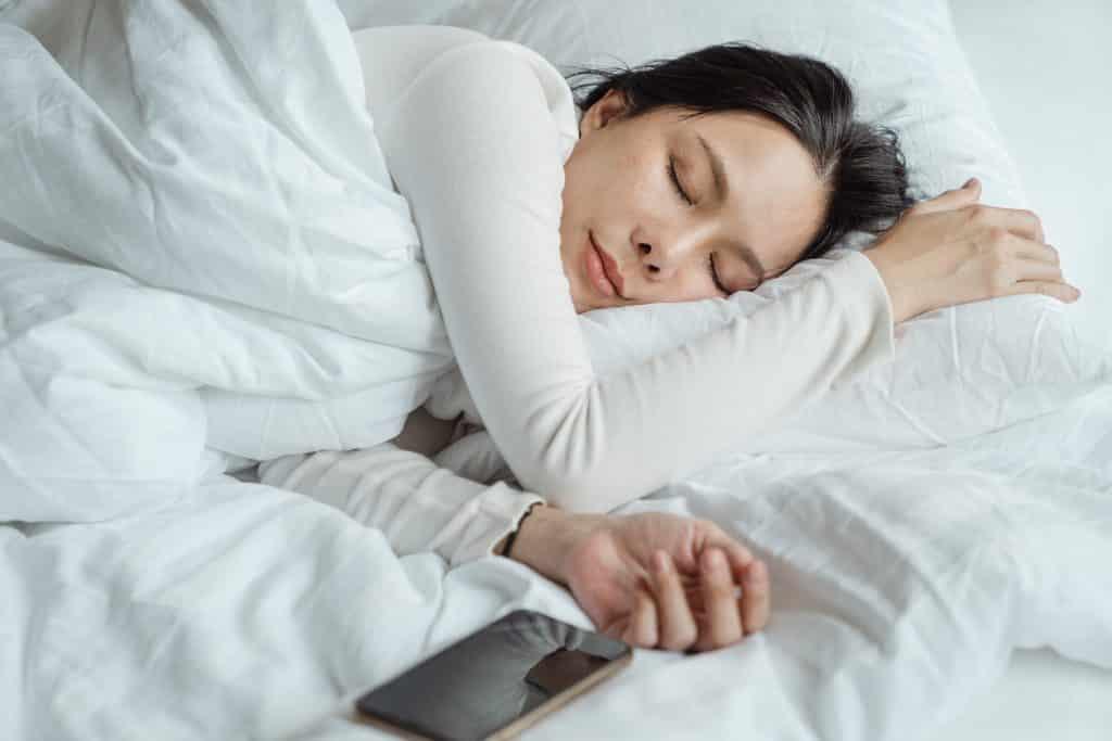 Mulher em sua cama com seu celular à sua frente