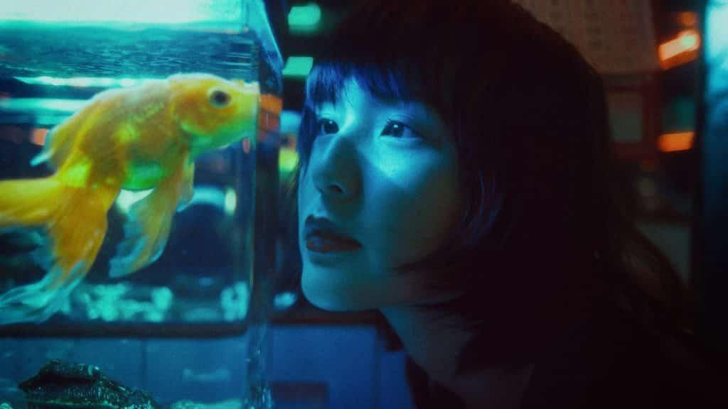 Mulher asiática olhando um aquário.