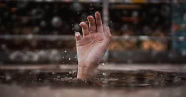 Uma pessoa se afogando esticando sua mão acima do nível da água