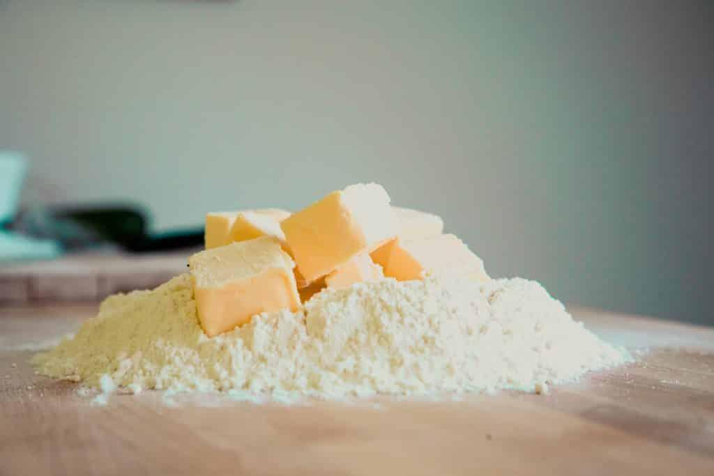 Pedaços de manteiga em cima de um montante de farinha de trigo