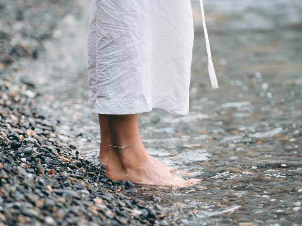 Mulher pisando descalça no chão.