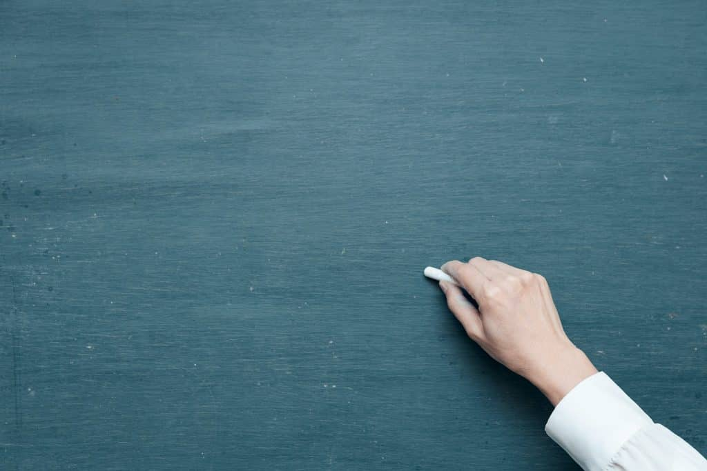 Um pessoa segurando um giz e escrevendo em um quadro negro