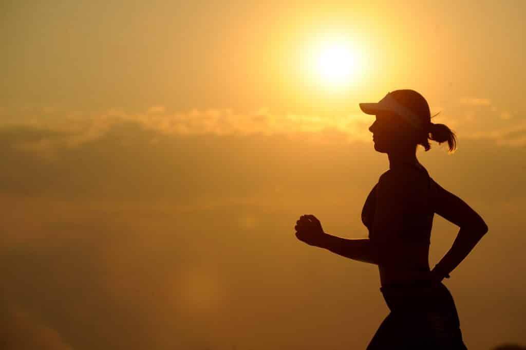 Uma mulher correndo em frente ao pôr do Sol