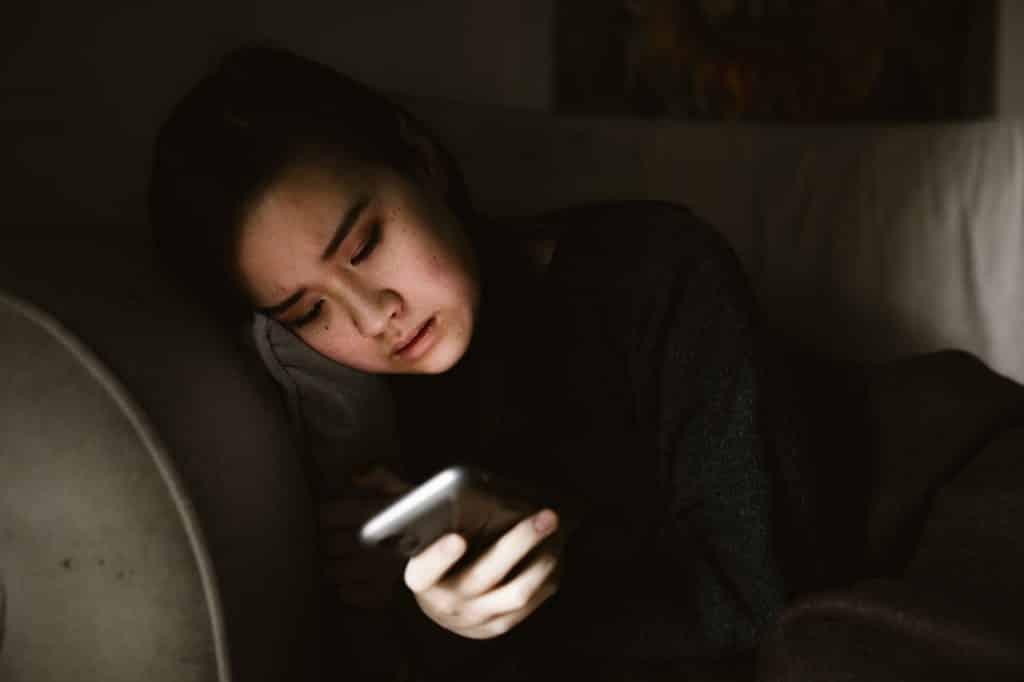 Mulher com semblante triste olhando para o celular.