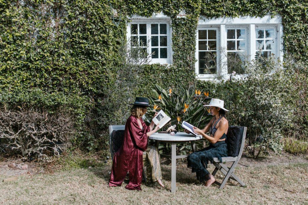 Mulheres sentadas em um jardim lendo.
