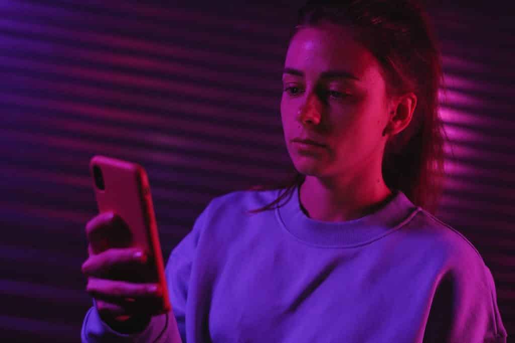 Menina olhando para o celular com semblante triste.