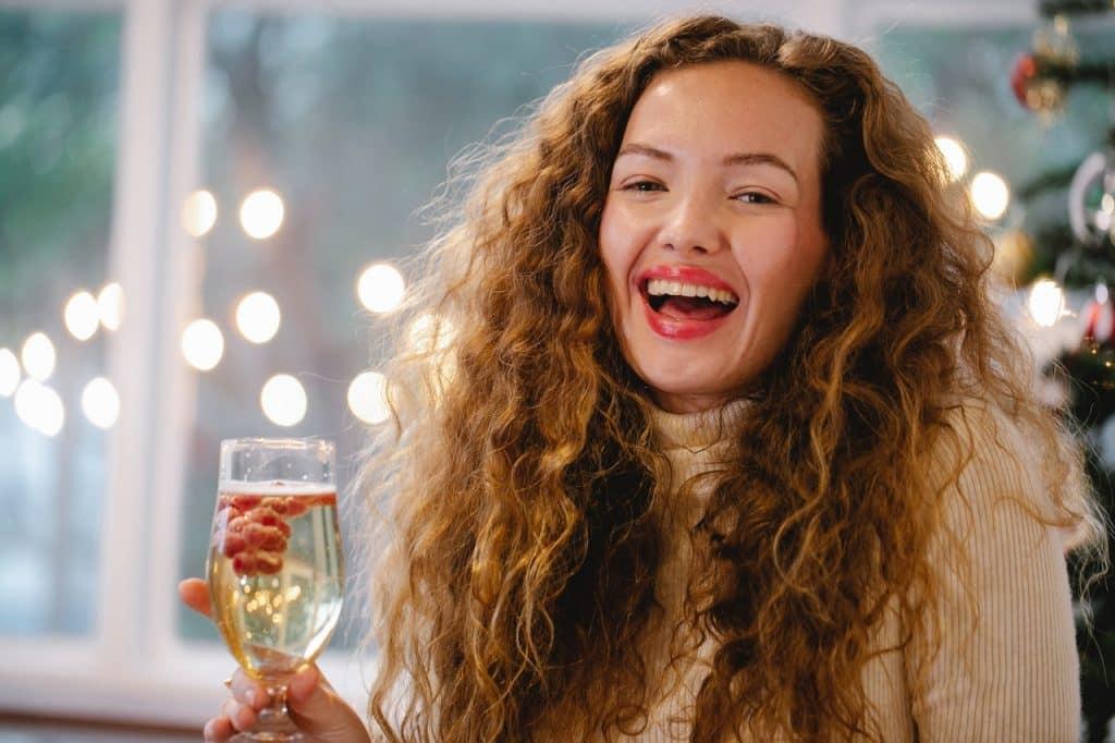 Mulher sorrindo com uma taça de champanhe na mão.