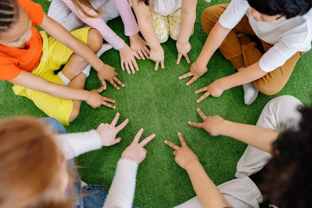 Crianças sentadas no chão em círculo com suas mãos ao centro