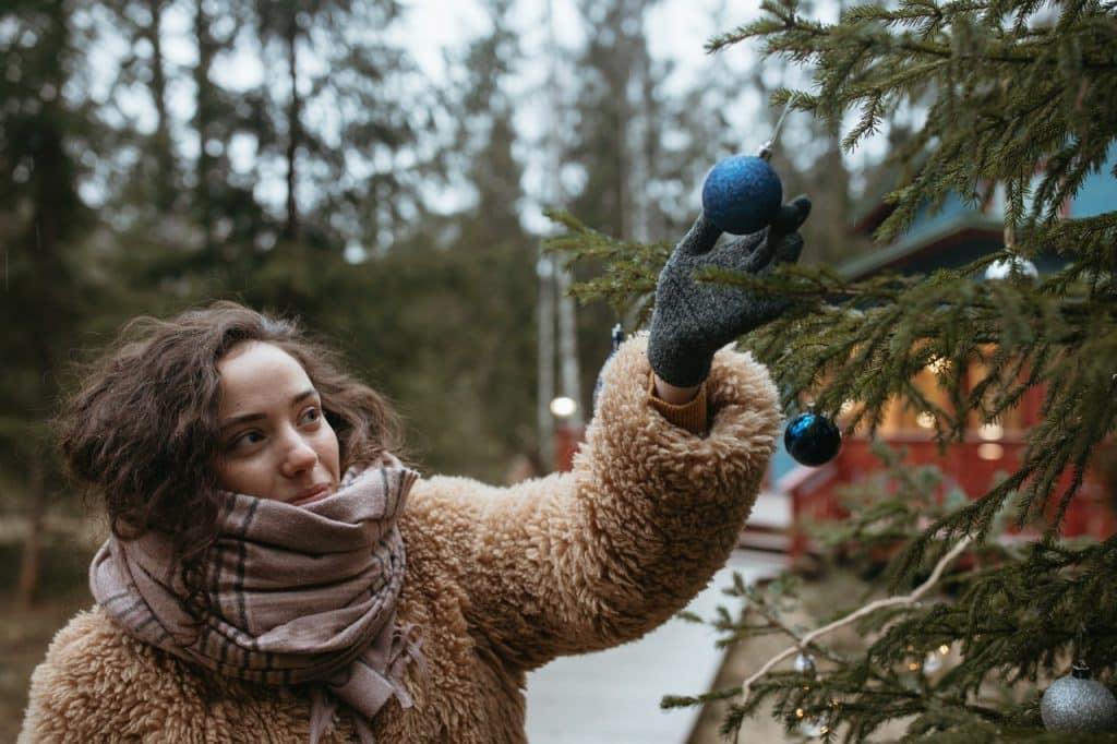 Menina tocando um enfeite de natal azul.