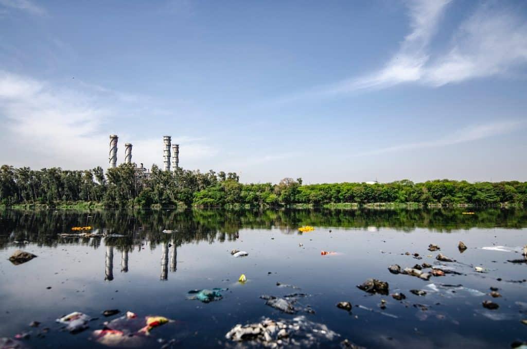 Rio de água corrente poluído por materiais de plástico, tecido, entre outros.
