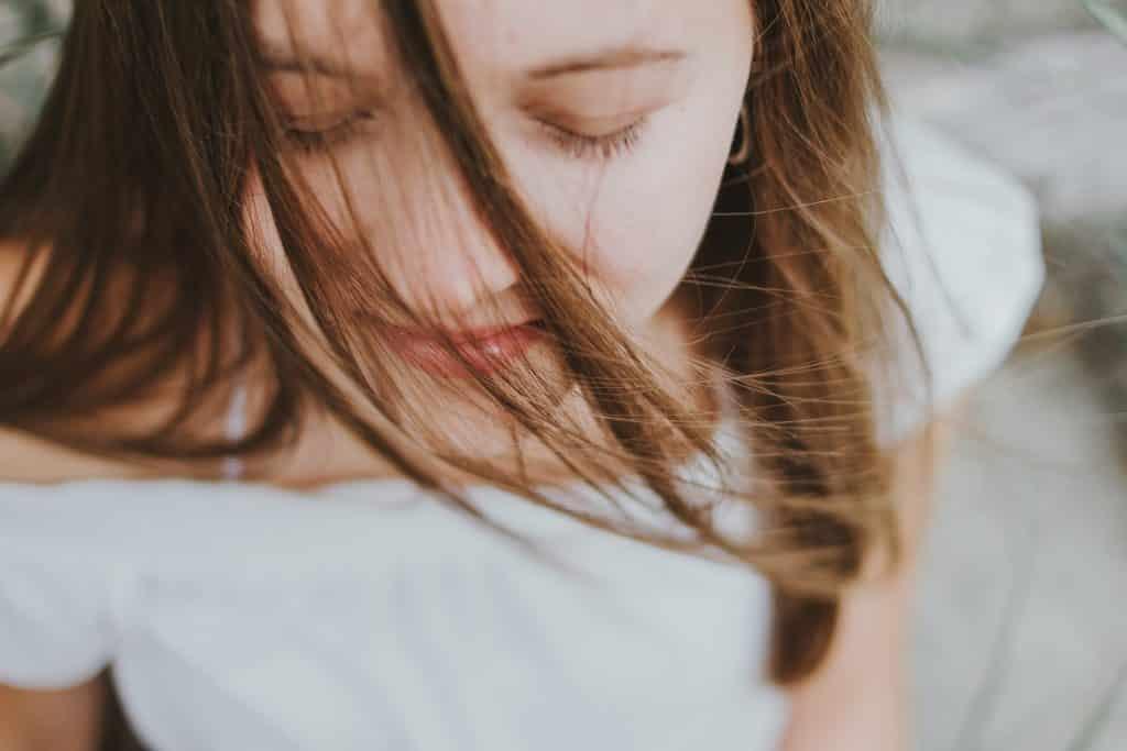 Mulher branca de olhos fechados e cabelos no rosto.