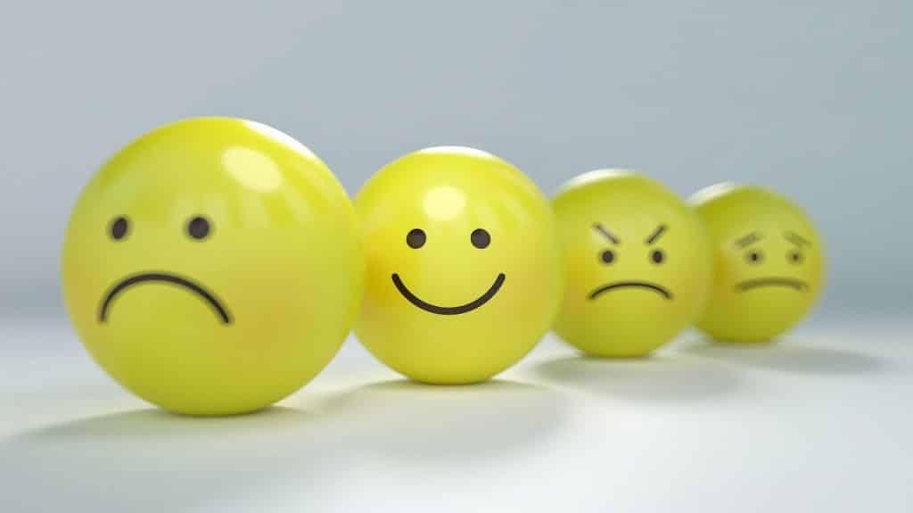 Três bolinhas com desenhos de expressões para representar emoções