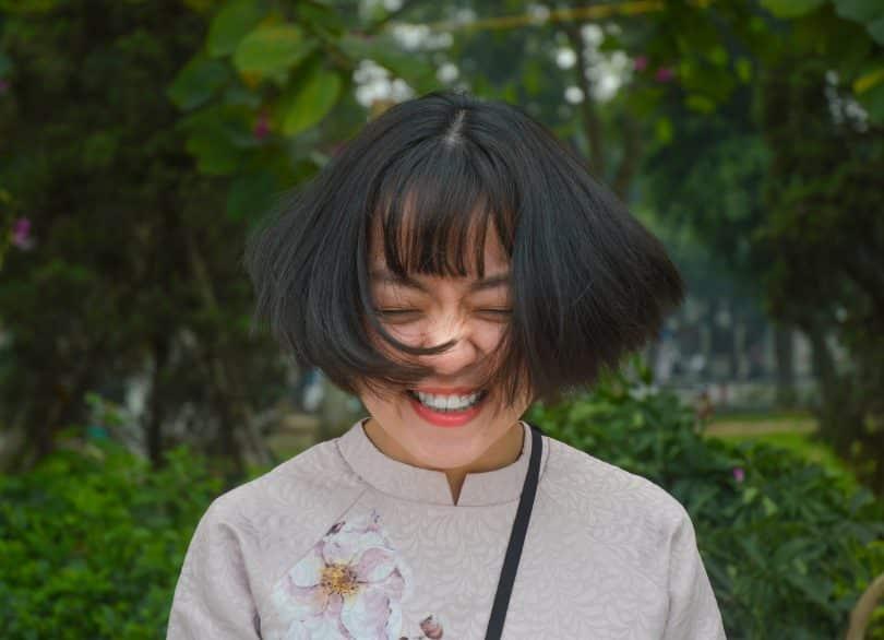 Mulher asiática sorrindo e com os cabelos balançando.