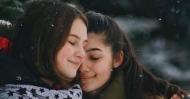 Mulheres brancas abraçadas.