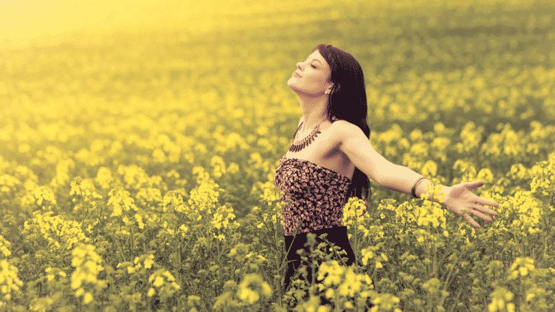 Mulher com os braços abertos em campo de flores