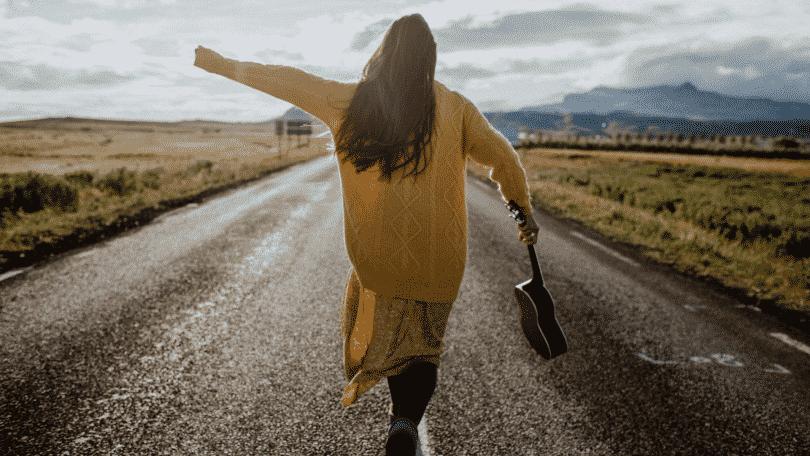 Mulher caminhando de braços abertos na estrada