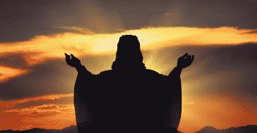 Silhueta de jesus cristo de braços abertos durante o por do sol