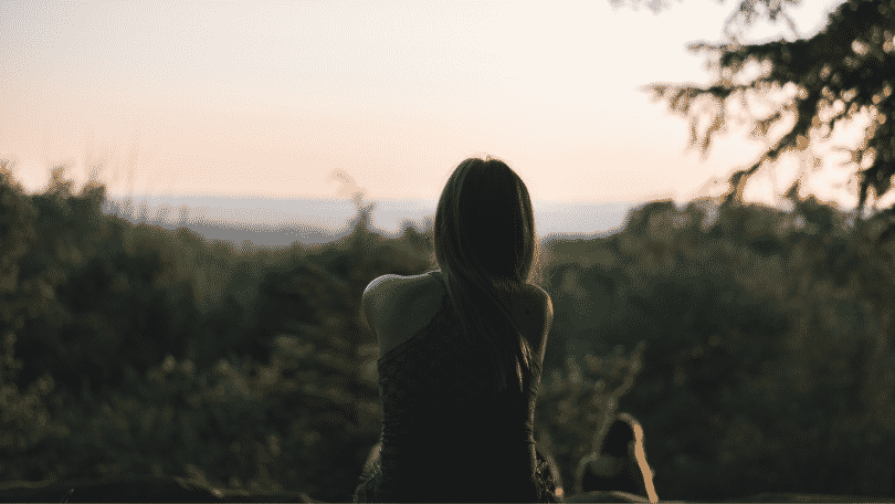 Silhueta de mulher sentada na montanha