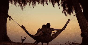 silhueta de casal abraçados e balançando na rede